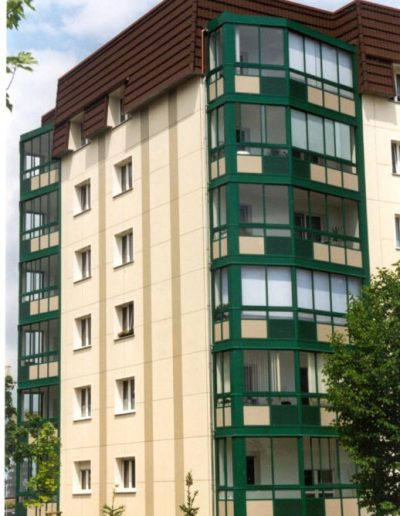 Moderne Fassadenverglasung an Mehrfamilienhaus in Farbe